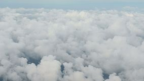 4K Aerial view above clouds from airplane window with blue sky stock footage