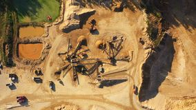 4K. Aerial view of a large sand quarry in working process with heavy machinery: sorting conveyor, bulldozers, excavators, trucks