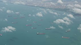 4K Aerial view of many container ships anchored at water area against port terminals stock video footage