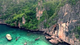 4k aerial view on marvelous seascape of giant stone rock with green tropical forest near turquoise blue ocean water stock video footage