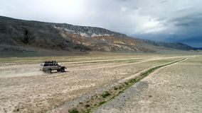 4K aerial view of safari vehicle driving on sand track road in the Altay Mountain. 4K aerial view of safari vehicle driving on sand track road in the Altai stock video