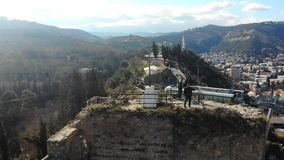 4k aerial view of the top of Narikala fortress, cross and tourists on peak. Cityscape on the background and a beautifyl sunny day in spring time stock video