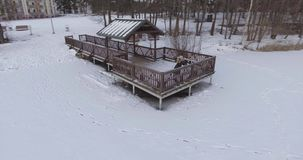 4K aerial view of young woman go down and stay on wooden dock covered with ice on frozen lake in cold winter day. stock video footage