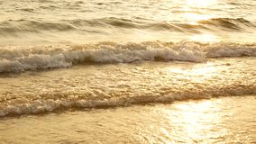 4K amazing sunset over the tropical beach. ocean beach waves on beach at sunset time , sunlight reflect on water surface. Beautiful evening nature sea stock footage