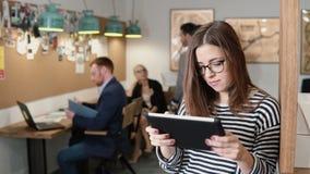4K använder den unga attraktiva brunettaffärskvinnan för closeupen en pekskärmminnestavla i det moderna startup kontoret Royaltyfria Foton
