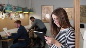 4K använder den unga attraktiva brunettaffärskvinnan för closeupen en pekskärmminnestavla i det moderna startup kontoret Arkivbilder
