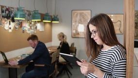 4K använder den unga attraktiva brunettaffärskvinnan för closeupen en pekskärmminnestavla i det moderna startup kontoret royaltyfri fotografi