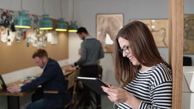 4K använder den unga attraktiva brunettaffärskvinnan för closeupen en pekskärmminnestavla i det moderna startup kontoret Royaltyfri Foto