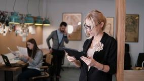 4K använder den unga härliga blonda affärskvinnan för closeupen en pekskärmminnestavla i det moderna startup kontoret royaltyfri bild