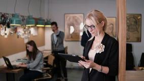 4K använder den unga härliga blonda affärskvinnan för closeupen en pekskärmminnestavla i det moderna startup kontoret royaltyfria bilder
