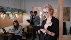 4K använder den unga härliga blonda affärskvinnan för closeupen en pekskärmminnestavla i det moderna startup kontoret royaltyfri fotografi