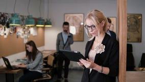 4K använder den unga härliga blonda affärskvinnan för closeupen en pekskärmminnestavla i det moderna startup kontoret Arkivbilder