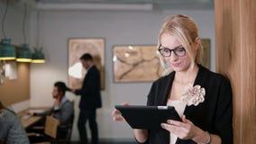 4K använder den unga härliga blonda affärskvinnan för closeupen en pekskärmminnestavla i det moderna startup kontoret royaltyfria foton