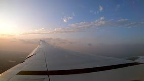 4K, asa do plano e por do sol alaranjado como visto através de uma janela do avião video estoque