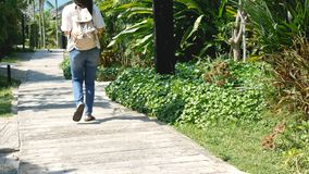 4K. Asian female tourist carrying rucksack walking on footpath to go to the sea. tourist enjoy in summer vacation on tropical. Country stock footage