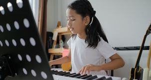 Asian little girl learning to play basic piano by using electric synthesiser keyboard for beginner music instrumental self studyin