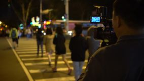 4K Asian operator with a video camera recording pedestrians crossroad night stock video footage