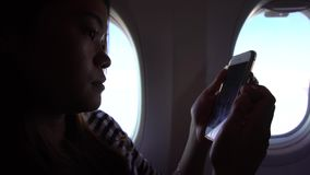 4k Asian woman holding the smartphone with hands during the flight. Young traveller sit down inside the plane using her phone device to writting a text message stock footage