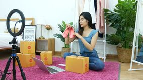 4K. Asian woman live streaming for selling shoe, fashion accessories online on social media via mobile phone from bedroom at home.