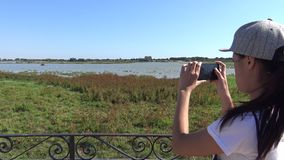4K, Asian Woman taking photograph with smartphone of marsh in Doñana stock footage