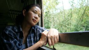 4K. asian woman travel by train looking out of a train window on railway train start at Bangkok go to Kanchanaburi in Thailand. Enjoy transportation by vintage stock video footage