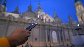4K, Asian woman using smartphone with the Cathedral-Basilica of the Pillar