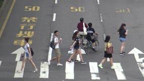 4K asiatiskt folk går över gatan i den Taipei staden, genom att använda paraplyet arkivfilmer
