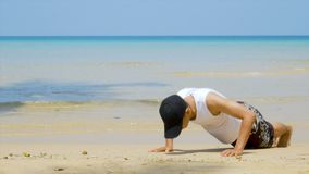 4K. athletic man workout by  push up at the sandy beach, part of his cross fitness workout. 4K. athletic man workout by  push up at the sandy beach, part of his stock footage
