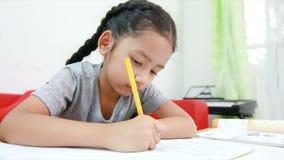 4K Aziatisch meisje die het huiswerk aangaande de lijst voor onderwijsconcept doen stock footage