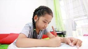 4K Aziatisch meisje die het huiswerk aangaande de lijst voor onderwijsconcept doen stock videobeelden