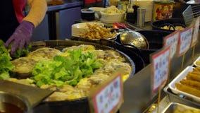 4k Aziatische mensen die beroemde oestersomelet in de nachtmarkt van de voedseltribune koken stock videobeelden