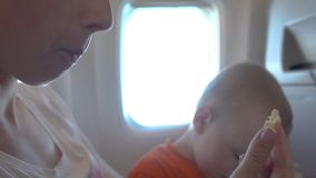4k - Baby feeds mom cookies while sitting on board. Cute baby enthusiastically feeds mom cookies while sitting on board. Action in real time stock footage