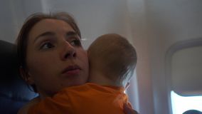 4k - Baby hugs his mom aboard a plane. Baby hugs his mom aboard a plane. He sits in her hands. Action in real time stock footage