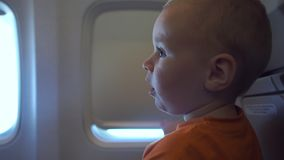 4k - The baby is trying to open the curtain window in the plane. The baby is trying to open the curtain window in the plane. Mom shows baby how to do it. Action stock footage