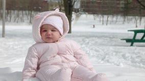 4K babymeisje die sneeuw voor het eerst ervaren stock footage
