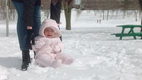 4K babymeisje die sneeuw voor het eerst ervaren stock videobeelden