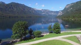 4K Baixo voo acima de surpreender o vale do lago Bohinj na manhã Montes verdes e águas profundas azuis Montanhas de Julian Alps vídeos de arquivo