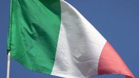 4K Bandera italiana que agita en el viento en un cielo azul Indicador de Italia metrajes