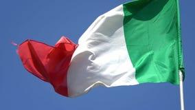 4K Bandera nacional de Italia que agita en viento en un cielo azul Indicador italiano metrajes