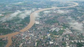 4K. Bangkok city view with Chao Phraya river from plane over the cloud. view from window seat on airplane over Bangkok cityscape.