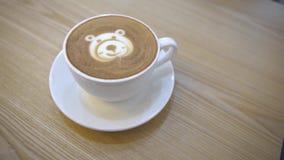 4K Barista fêmea que serve a arte do café no coffeeshop com uma forma do urso da cara filme