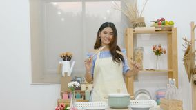 4K. beautiful Asian woman hold ladle dancing in the kitchen , feeling enjoy for cooking behind dining table with pot stock video