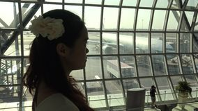 4k beautiful asian woman is looking the plane in Thailand airport stock video footage