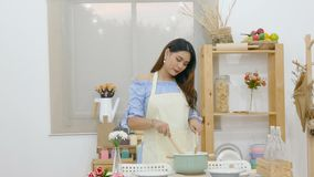 4K. beautiful Asian woman use ladle stirring soup behind dining table with pot , dish and kitchenware in the kitchen room stock video footage