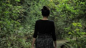 4k beautiful girl in black handmade skirt squares textures, defile on a wooden way deep in the green forest in. 4k beautiful girl in balck handmade skirt squares stock video footage