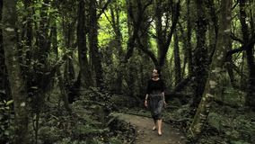 4k beautiful girl in black handmade skirt squares textures, defile on a wooden way deep in the green forest in. 4k beautiful girl in balck handmade skirt squares stock video