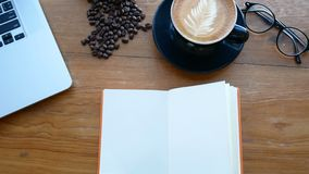 4K. blank white book on wooden table, page flip from wind. book at work space with notebook , cup of coffee and glasses stock video
