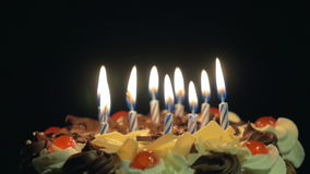 4k - Blowing out birthday candles on a spinning delicious chocolate cake stock video