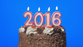 4k - Blowing out new year 2016 candles on a delicious chocolate cake, blue screen stock footage