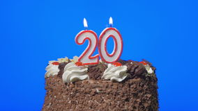 4k - Blowing out number twenty birthday candles on a delicious chocolate cake, blue screen stock footage